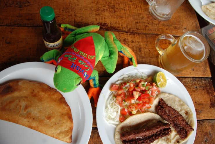Javi the Frog about to dig into an empanada with a beer