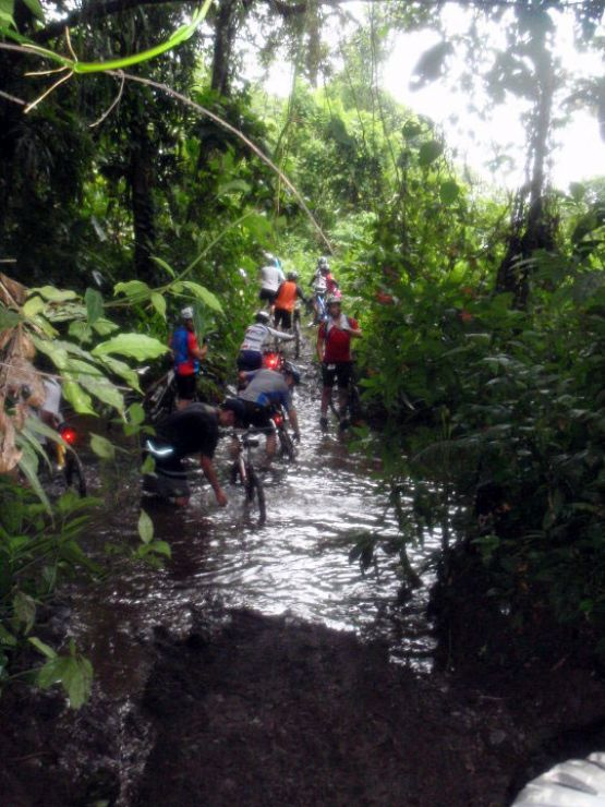 Mountain Biking through a river during Ciclismo Earth Costa Rica