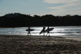 Walking to surf at Playa Langosta - Playa Langosta, Guanacaste