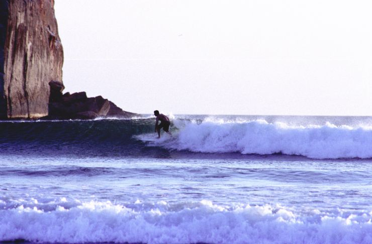 Surfer on the right wave at the famous Witch's Rock in Santa Rosa National Park
