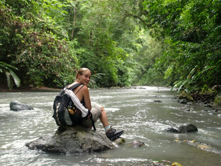 Hiker on rock in river inside Corcovado National Park