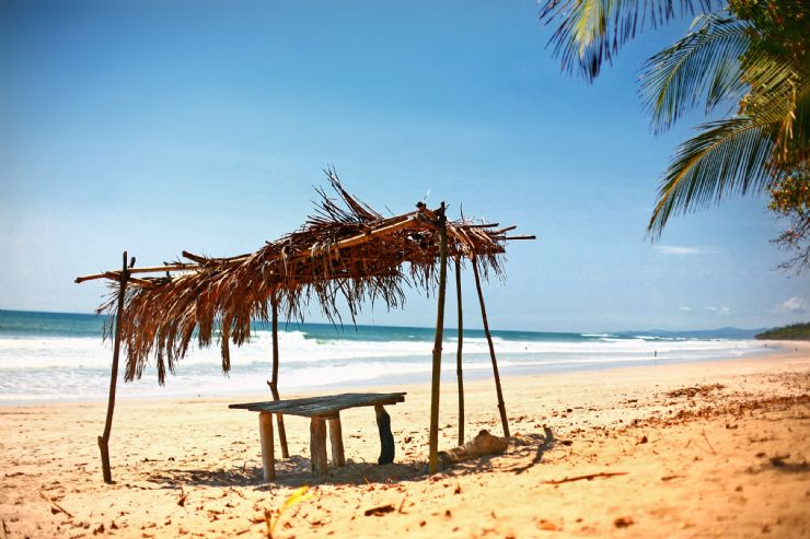 Palm thatched roof in front of the surf break at Santa Teresa
