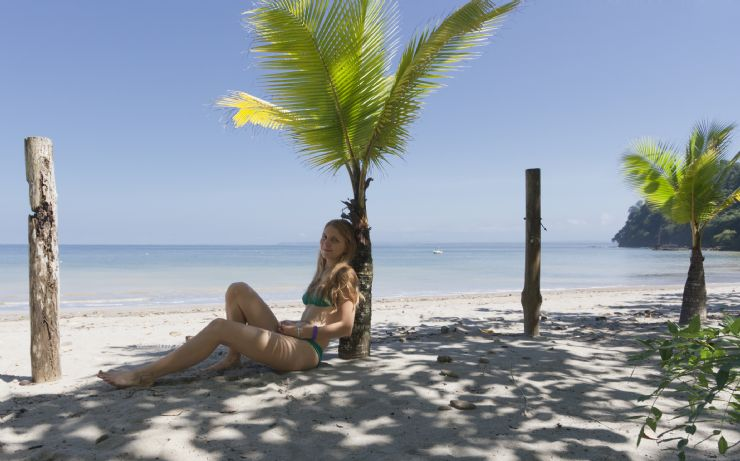 Girl leaning on a post on the beautiful Punta Leona beach