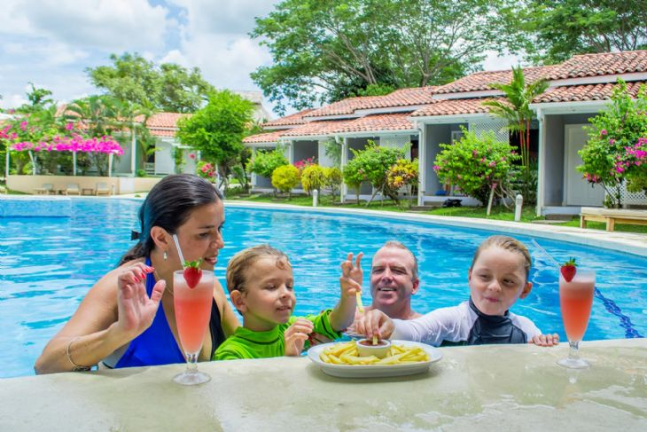 Family enjoying the pool and food